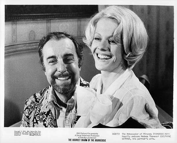 Fernando Rey with Delphine Seyrig on his lap in a scene from the film 'The Discreet Charm of The Bourgeoisie', 1972. (Photo by 20th Century-Fox/Getty Images)
